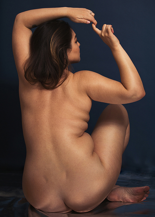 boudoir photography of plus size nude woman's back, nude portrait celebrating plus size body rolls, studio boudoir with blue background.