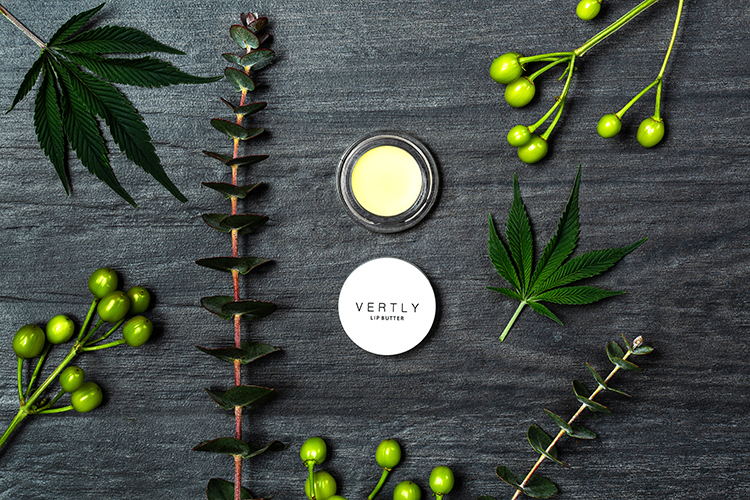 Styled product photo, CBD beauty product photography. Lip Butter with cannabis leaves, and greenery on slate