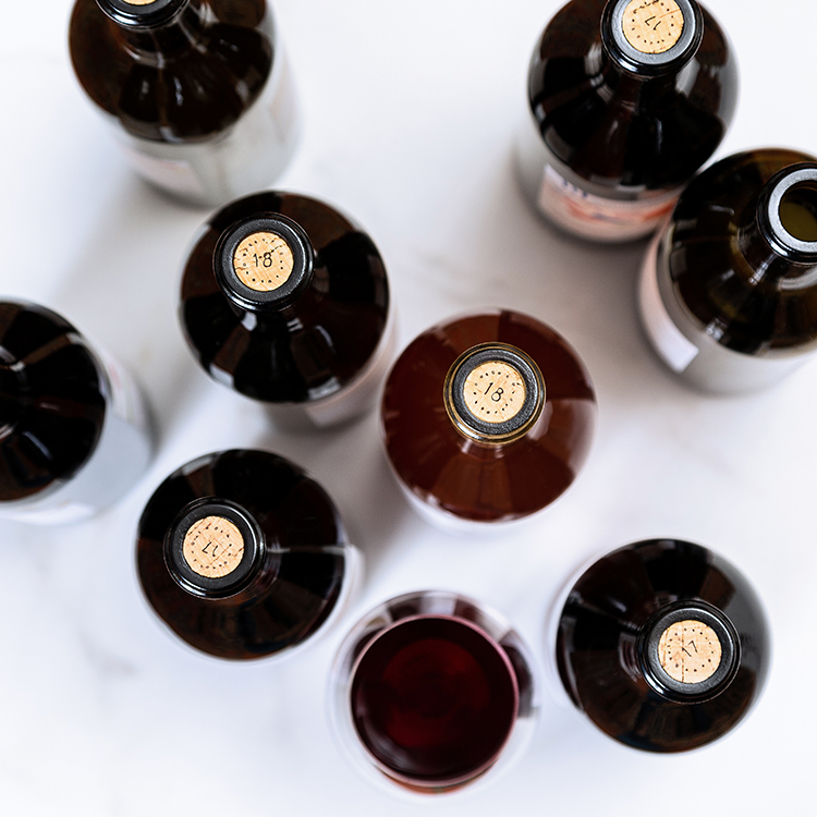 top down view of wine bottles and wine glass. Product Photography for Central california winery. Wine bottles standing on marble counter. Photographed by Ella Sophie, bay area product photographer.