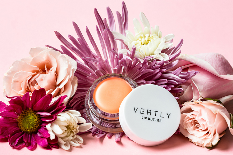 Pink spring beauty product styled photo. CBD beauty product, lip balm, with spring flowers around it. Promotional product photography by Ella Sophie, Oakland CA