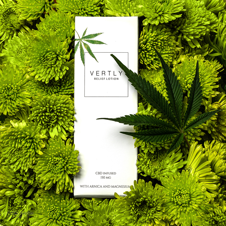 CBD Beauty Product Photography, CBD product photographer Ella Sophie, cbd lotion box arranged on green flowers with cannabis leaf.