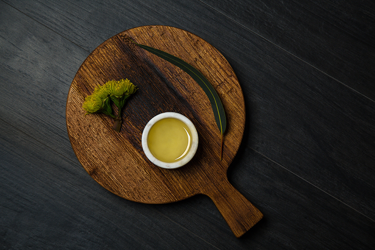 Simple styled image of oil for facial serum. Oil with slate, wood board and greenery. Yellow oil. Photographed by Ella Sophie, SF bay area product photographer.