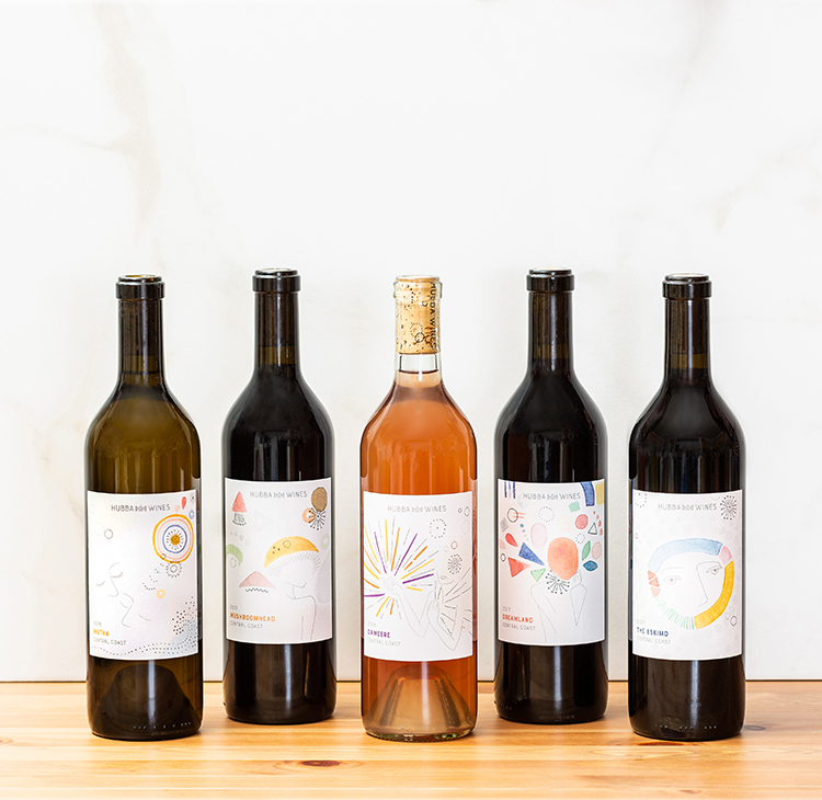Collection of wine bottles photographed on a table with white marble background. Product photography by Ella Sophie, Oakland CA.